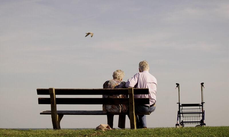 Gemeinsam Alt werden - Pärchen sitzt auf einer Parkbank und schaut in die Ferne