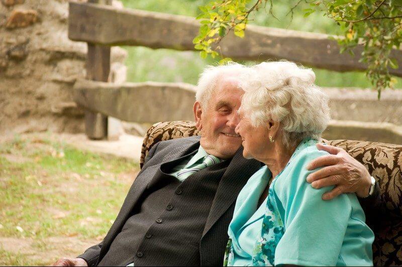 Ein älteres Pärchen sitzt gemeinsam auf der Bank im Park oder Friedhof und hält sich im Arm.