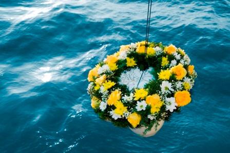 Seebestattung - der Verstorbene wird mit einem Blumenkranz bedeckt zu Wasser gelassen