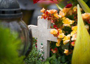 Bestattungsdienst aus Stuttgart - Steinkreuz umringt von Blumen auf dem Friedhof