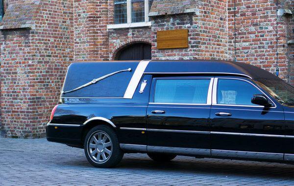 Bestattungskraftwagen in schwarz steht vor einer Kirche bei einer Beerdigung