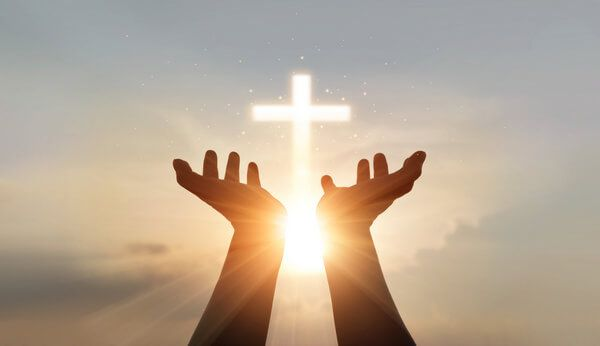 Christliche Bestattung - Die Hände halten ein Kreuz