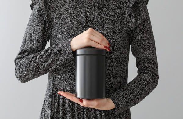 Einäscherung - Mann hält eine schwarze Urne in der Hand