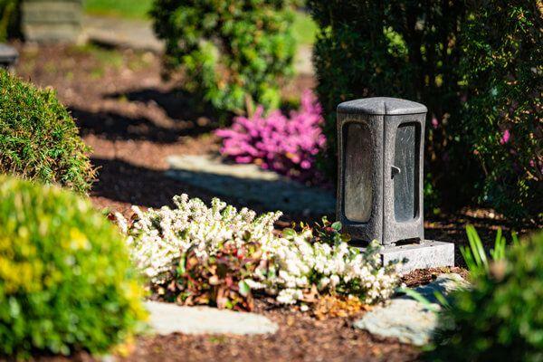 Grab mit Kerze und schönem Blumenschmuck am Grab