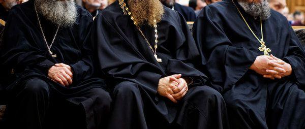 Orthodoxe Bestattung - Priester sitzen auf einer Bank - Kreuz auf einer Kette