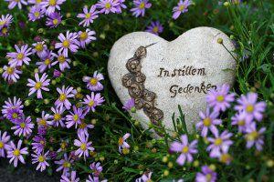 Stein Herz im Blumen für eine Trauerfeier