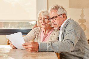 Vorsorge - älteres Pärchen liest den Bestattungs-Vorsorgeplan gemeinsam durch