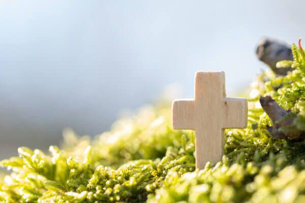 Weißes Kreuz in Blumen für eine Bestattung