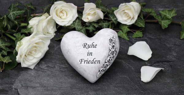 Weisse Rosenblätter umranden ein Herz mit der Aufschrift - Ruhe in Frieden